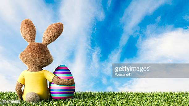 easter bunny sitting on grass with arm around easter egg - easter bunny stock illustrations