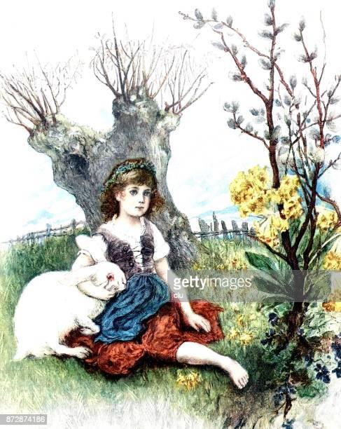 Pasen scène: meisje zit met een konijn in de weide omringd door bloemen