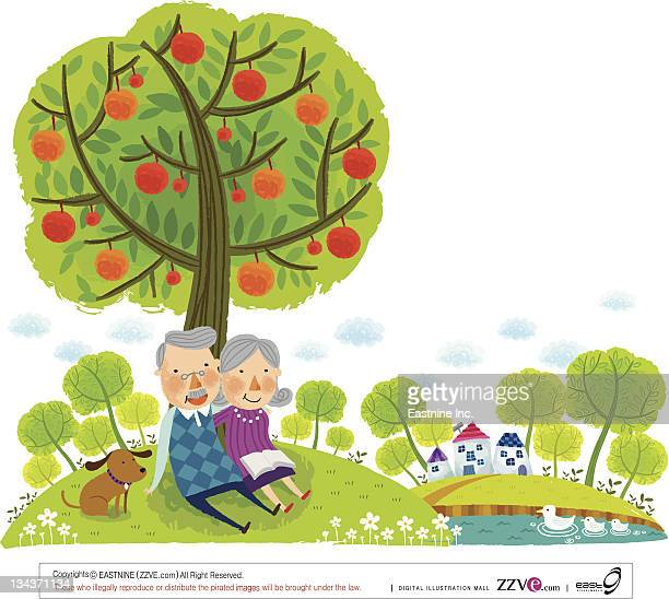 Elderly couple sitting under tree