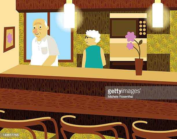 Elderly man and woman in wallpapered kitchen