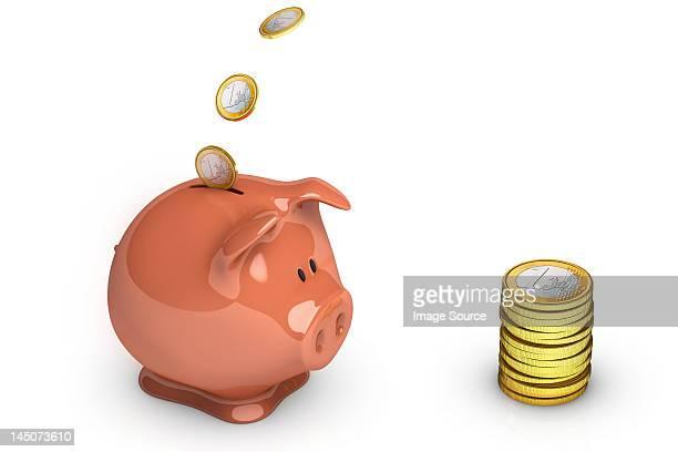 Euro coins going into piggy bank