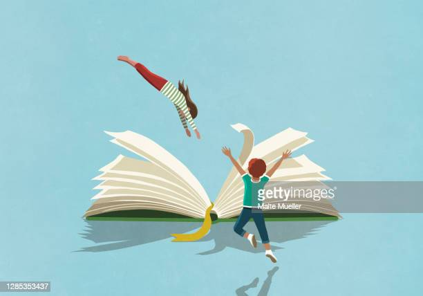 exuberant boy watching girl dive into book - ideas stock illustrations