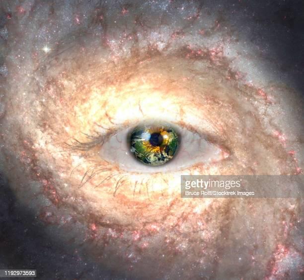 ilustraciones, imágenes clip art, dibujos animados e iconos de stock de eye in midst of galaxy with earth reflection. - galaxiaespiral