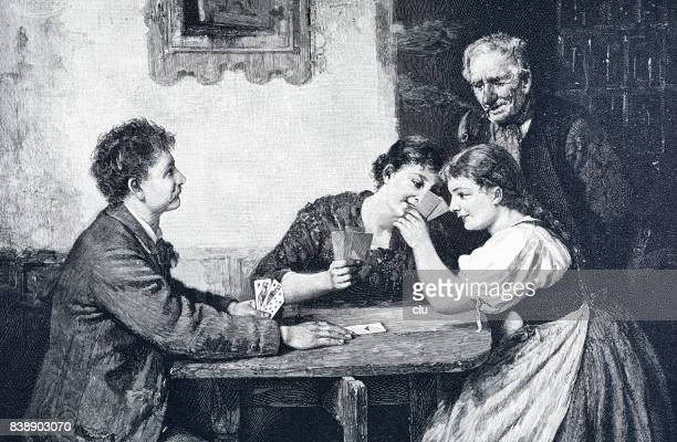 Family sitting in living room playing cards