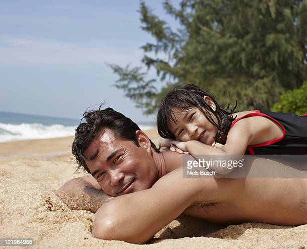 Father and daughter relaxing on beach
