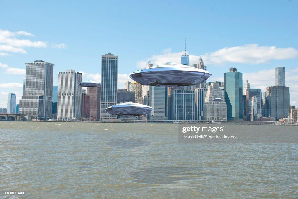 Flying saucers over New York harbor. 3D Rendering : stock illustration