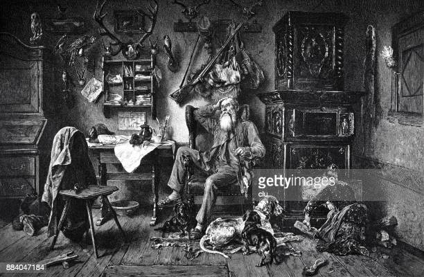 Forest ranger sits in his heated living room and smokes a pipe, the woman pushes wood into the oven.