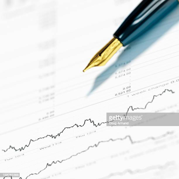 a fountain pen laying on financial papers - report stock illustrations