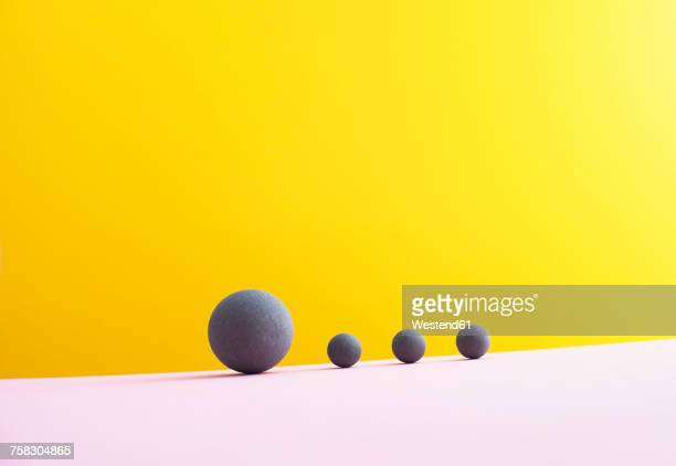 four spheres against yellow background, 3d rendering - scale stock illustrations