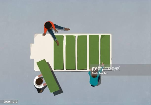 friends assembling green battery - order stock illustrations