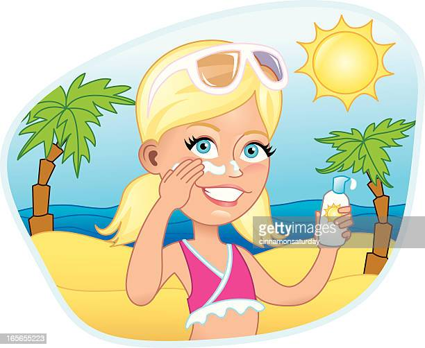 Girl putting on sunscreen at the beach