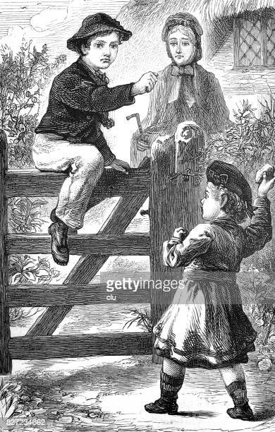 Girl throwing a lump of earth to a boy sitting on fence