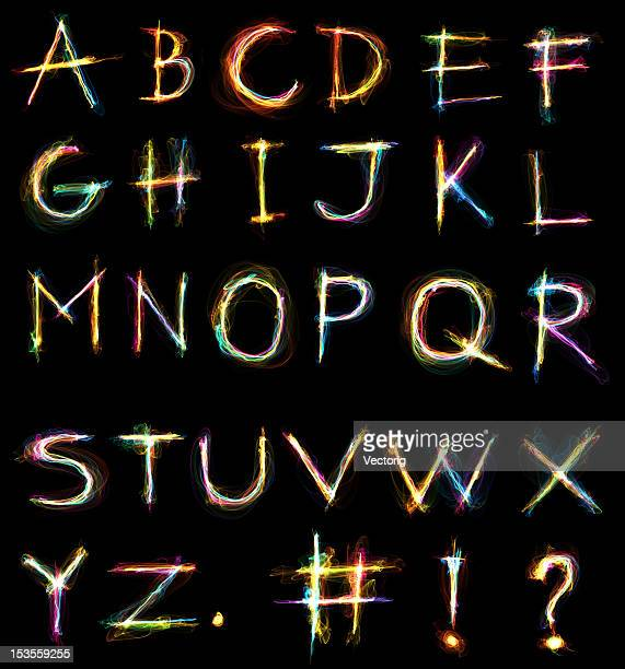Glowing alphabet over a black background