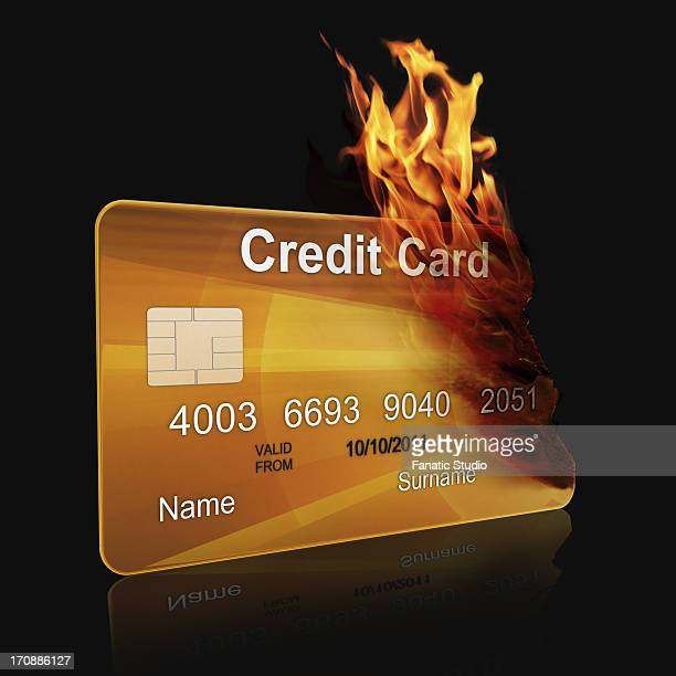 A gold credit card burning over black background