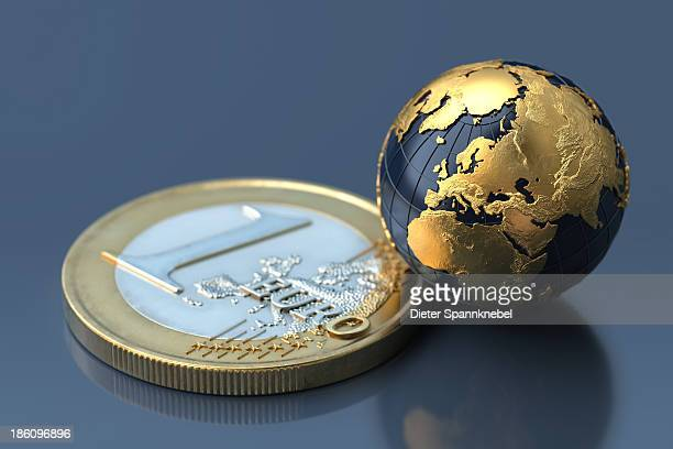 Golden globe beside a one euro coin