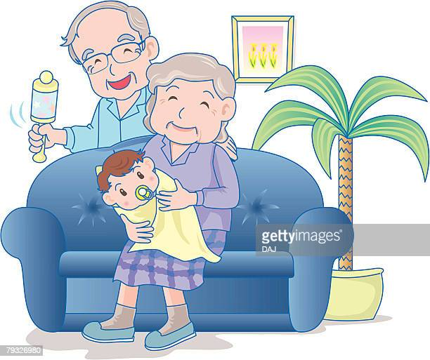 Grandfather and grandmother with baby on sofa, smiling