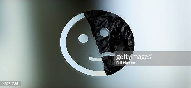 Graphic of a face half smiling and half sad against a gradient background
