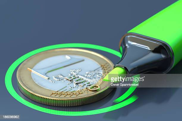 Green highlighter beside a one euro coin
