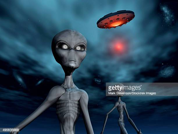 Grey Aliens and their flying saucer, visiting Earth.