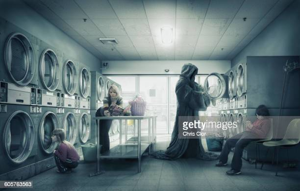 grim reaper doing laundry at laundromat - family stock illustrations