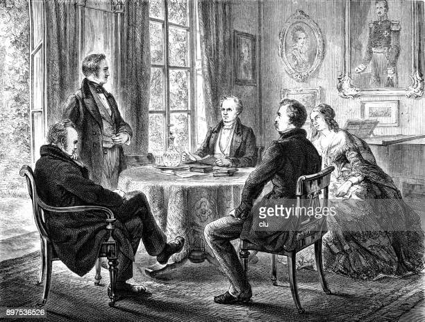 Group of persons sitting around a table reading and talking