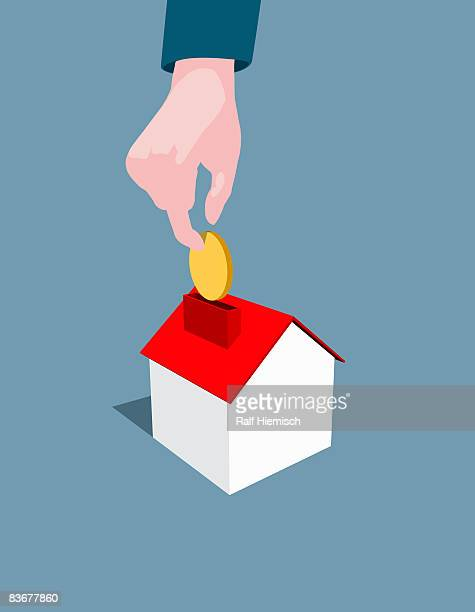 a hand dropping a coin into a house shaped money box - mortgage loan stock illustrations