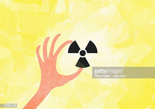 a hand holding a radioactive symbol - radioactive contamination stock illustrations