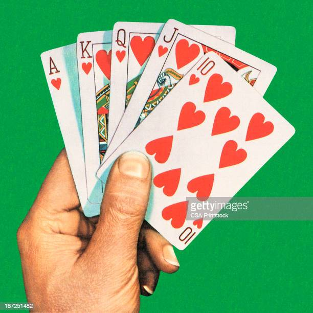 A hand holding a royal flush cards