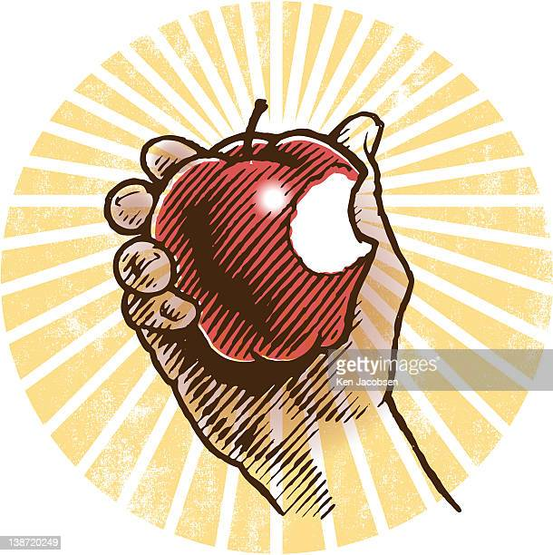 A hand holding an apple with a  bite in it
