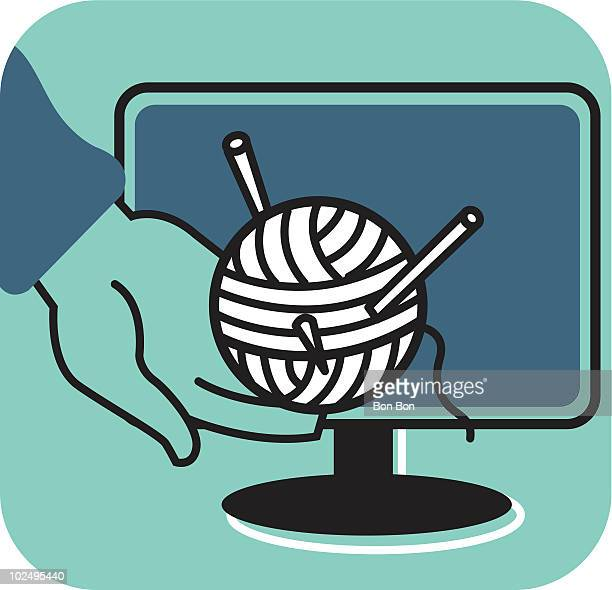 Hand holding ball of wool in front of computer monitor