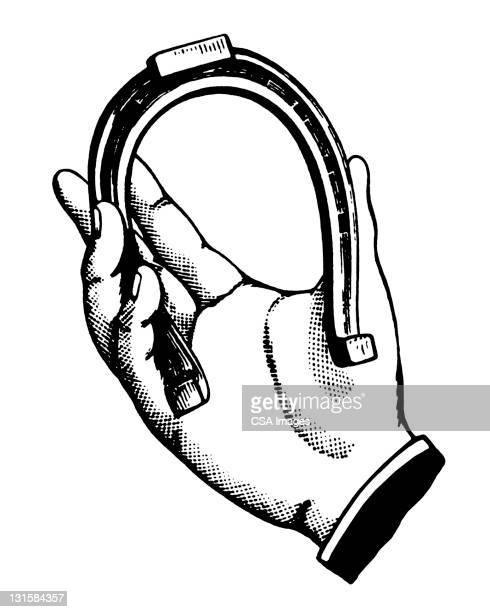 Hand Holding Horseshoe