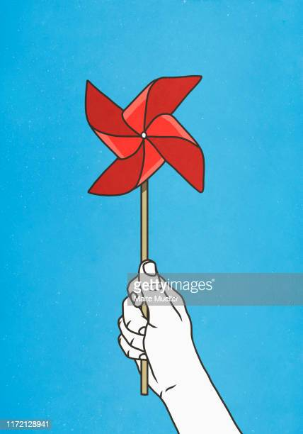 hand holding red pinwheel - unrecognisable person stock illustrations