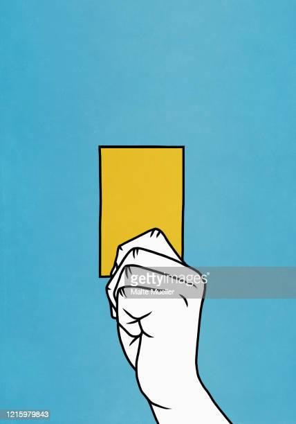 hand holding yellow card - yellow card sport symbol stock illustrations