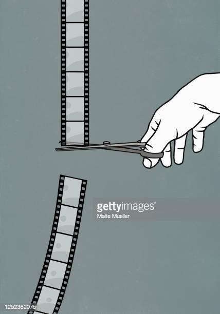 hand with scissors cutting film negative - film stock illustrations