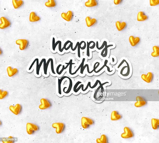 hand-made composition of gold and red hearts with handwritten text happy mothers day - beautiful original love card design - mothers day text art stock illustrations