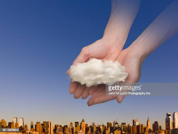 Hands of caucasian woman holding cloud over New York skyline, New York, United States