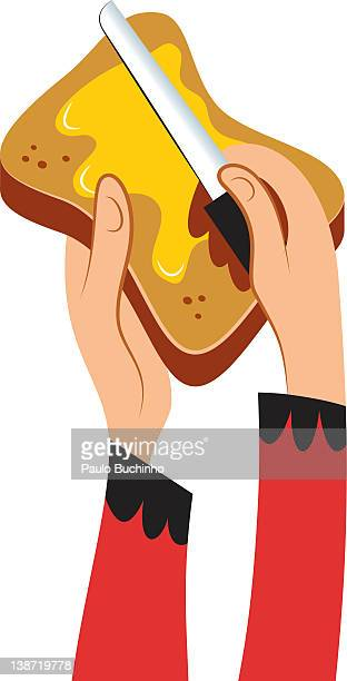 Hands spreading butter on toast