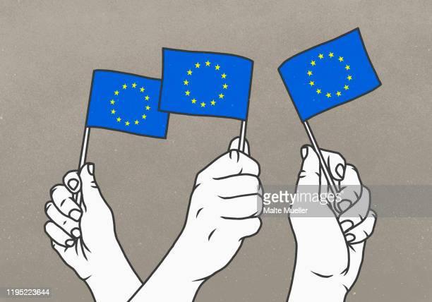 illustrazioni stock, clip art, cartoni animati e icone di tendenza di hands waving small european union flags - la comunità europea