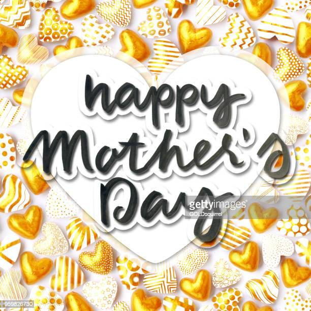 handwritten text happy mother's day placed above in the middle of big white paper heart located above seamless pattern made of golden hearts - original love card design - mothers day text art stock illustrations