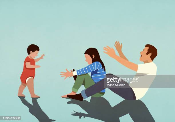 happy couple cheering for baby son taking first steps - baby stock illustrations