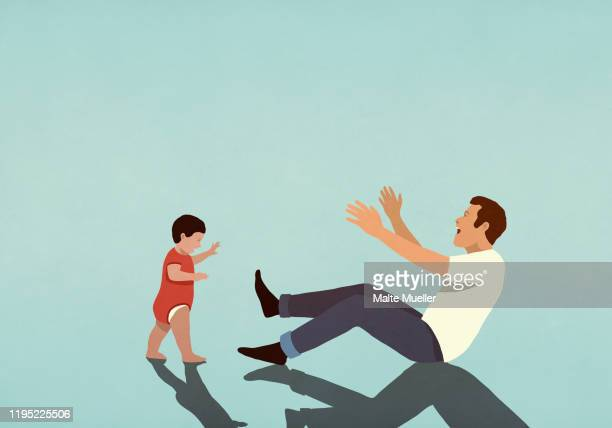 happy father cheering for baby son taking first steps - family stock illustrations