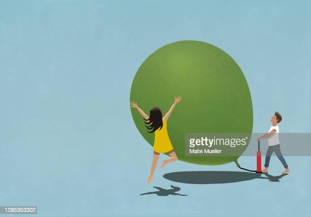 illustrazioni stock, clip art, cartoni animati e icone di tendenza di happy man and woman inflating large balloon - giovane adulto