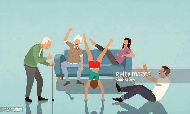 happy multi-generation family cheering for girl doing handstand in living room - illustration stock illustrations
