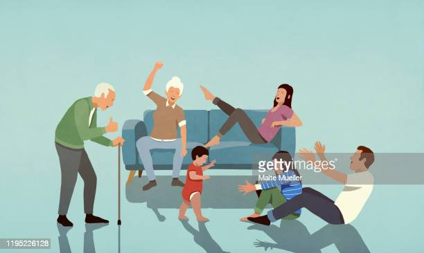 happy multi-generation family cheering in living room - family stock illustrations