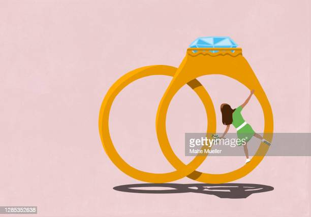 happy young woman hanging from engagement ring - rear view stock illustrations