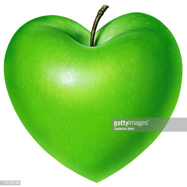 Heart shaped green apple against white background
