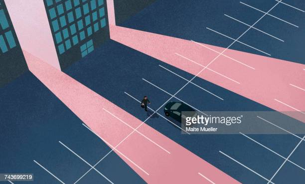 High angle view of man walking towards car at parking lot against building