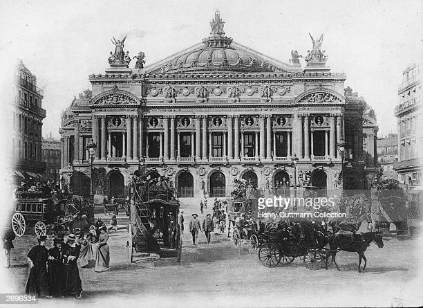 Horsedrawn buses amongst traffic outside the opera house in Paris