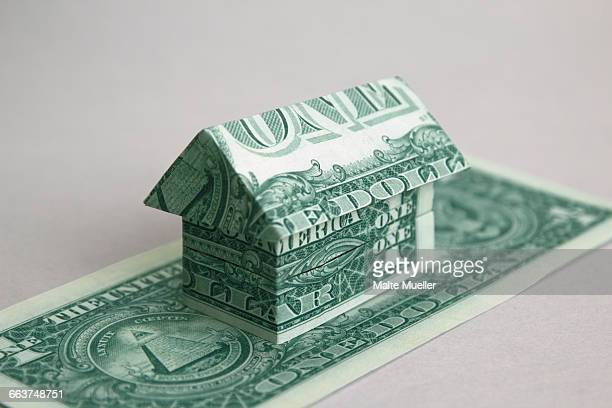 House made of one dollar US notes against white background