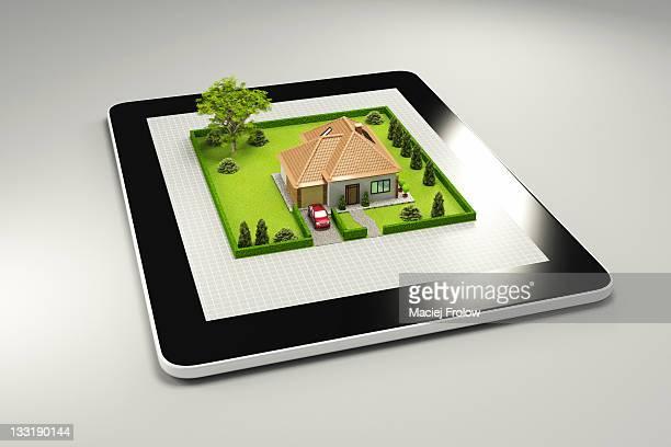 3D house on a tablets PC on grey floor
